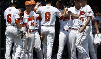 Sam Houston State's Carter Burgess (8) is congratulated by teammates after scoring on a hit Dylan Ebbs against Siena during an NCAA college baseball regional tournament game in Fort Worth, Texas, Sunday, June 1, 2014. (AP Photo/Jim Cowsert)