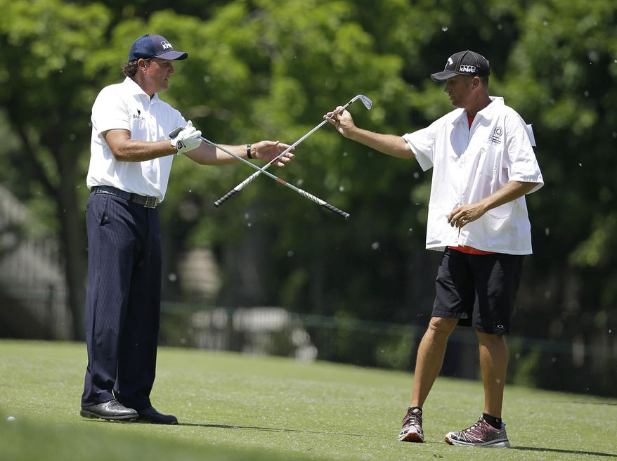 Phil Mickelson, left, exchanges clubs with his caddie Jim Mackay before his shot from the 13th fairway during the final round of the Memorial golf tournament on Sunday, June 1, 2014, in Dublin, Ohio. (AP Photo/Darron Cummings)