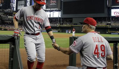 Cincinnati Reds' Zack Cozart (2) celebrates with Jay Bell (49) after hitting a first-inning solo home run against the Arizona Diamondbacks during a baseball game, Sunday, June 1, 2014, in Phoenix. (AP Photo/Rick Scuteri)