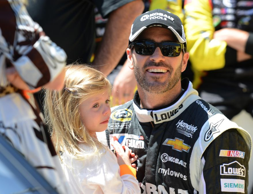 Jimmie Johnson holds his daughter Genevieve, left, before driving in the NASCAR Sprint Cup series auto race at Dover International Speedway, Sunday, June 1, 2014, in Dover, Del. (AP Photo/Molly Riley)