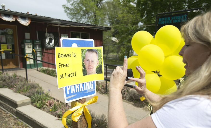 Diane Walker takes a picture of a sign celebrating U.S. Army Sgt. Bowe Bergdahl's release in front of Zaney's coffee shop in Hailey, Idaho. Bergdahl, 28, had been held prisoner by the Taliban since June 30, 2009. He was handed over to U.S. special forces by the Taliban in exchange for the release of five Afghan detainees held by the United States. (AP Photo/The Idaho Statesman, Kyle Green)