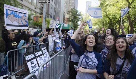 Marchers cheer as they pass along a barricade separating them from anti-Boycott, Divestment and Sanctions (BDS) movement protestors during the Celebrate Israel Parade, Sunday, June 1, 2014, in New York. Among the 35,000 marchers were New York Gov. Andrew Cuomo, New York City Mayor Bill de Blasio, Israeli diplomats and members of the Knesset, Israel's parliament. (AP Photo/John Minchillo) ** FILE **