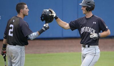 Long Beach State's Michael Hill, right, is congratulated by teammate Johnny Bekakis (2) after hitting a solo home run during the sixth inning of an NCAA college baseball regional tournament game against North Carolina in Gainesville, Fla., Sunday, June 1, 2014. (AP Photo/Phelan M. Ebenhack)