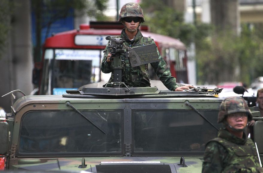 "A Thai soldier guards on top of a military vehicle with a machine gun outside a shopping mall where protesters gather for an anti-coup demonstration in Bangkok, Thailand Sunday, June 1, 2014. Hundreds of demonstrators shouting ""Freedom!"" and ""Democracy!"" gathered Sunday near a major shopping mall in downtown Bangkok to denounce the country's May 22 coup despite a lockdown by soldiers of some of the city's major intersections. (AP Photo/Wason Wanichakorn)"