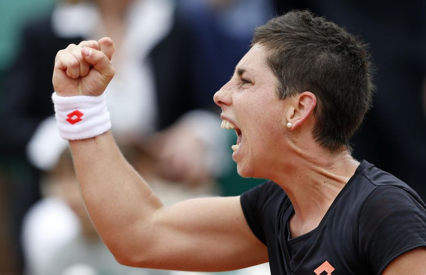 Spain's Carla Suarez Navarro reacts as she  defeats Croatia's Ajla Tomljanovic during their fourth round match of  the French Open tennis tournament at the Roland Garros stadium, in Paris, France, Sunday, June 1, 2014. (AP Photo/Darko Vojinovic)