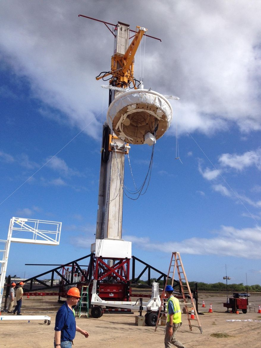 This April 23, 2014 image provided by NASA shows NASA's saucer-shaped experimental flight vehicle being prepared for a Range Compatibility Test at the at the U.S Navy's Pacific Missile Range Facility at Kekaha on the island of Kaua'i in Hawaii. The vehicle, part of the Low Density Supersonic Decelerator project, will test an inflatable decelerator and a parachute at high altitudes and speeds over the Pacific Missile Range scheduled  for June 1, 2014. (AP Photo/NASA)