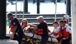A woman is rescued from the South Side stretch of Lake Michigan, Sunday, June 1, 2014, after a boat she was in capsized Saturday night miles from Chicago's shoreline. The U.S. Coast Guard said crews are searching for as many as four other people. (AP Photo/Sun-Times Media, Alex Wroblewski)