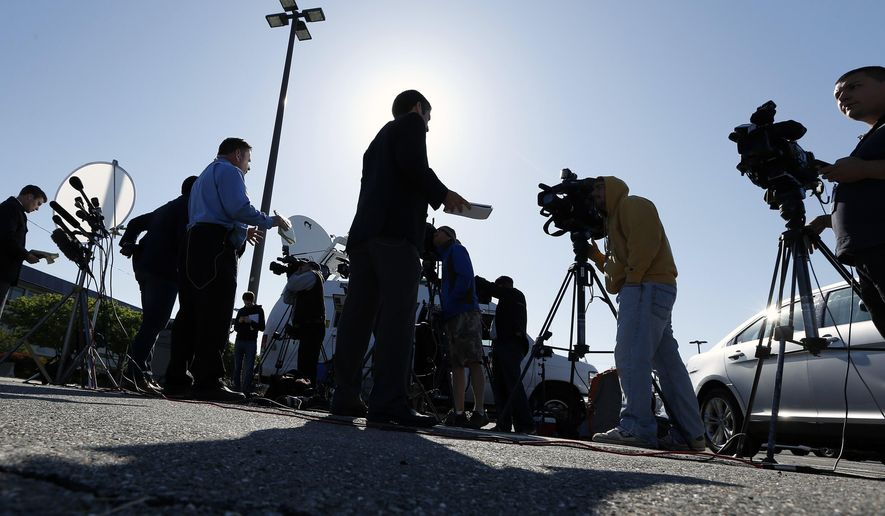 Reporters speak in front of television cameras while waiting for a news conference to begin at Hanscom Field in Bedford, Mass., Sunday, June 1, 2014. (AP Photo/Michael Dwyer)