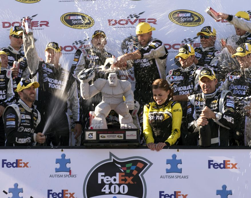 Jimmie Johnson, left, celebrates winning the NASCAR Sprint Cup series auto race at Dover International Speedway, Sunday, June 1, 2014, in Dover, Del. (AP Photo/Molly Riley)