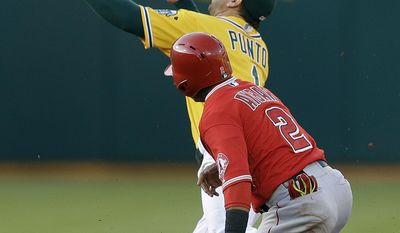 Oakland Athletics' Nick Punto (1) bobbles the ball as Los Angeles Angels' Erick Aybar slides safely into second base in the first inning of a baseball game Saturday, May 31, 2014, in Oakland, Calif. (AP Photo/Ben Margot)