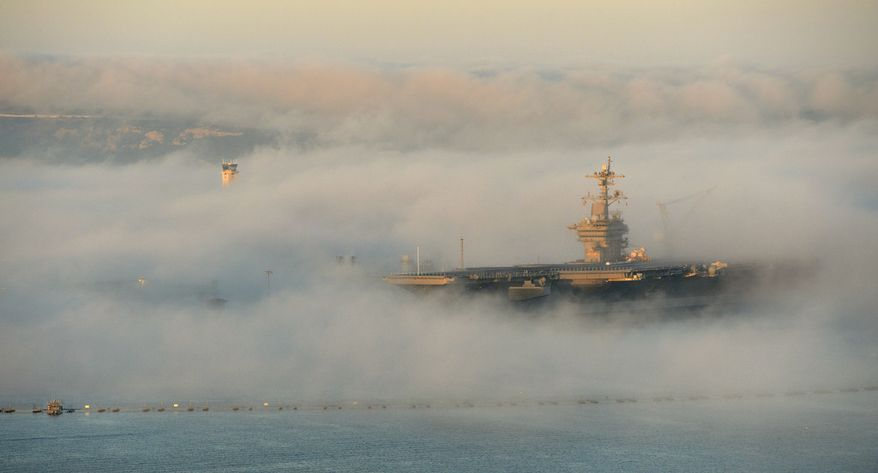 The aircraft carrier USS Carl Vinson (CVN 70) is enveloped in fog Feb. 11, 2014, as it sits in its berth in San Diego. (DoD photo by Glenn Fawcett/Released)