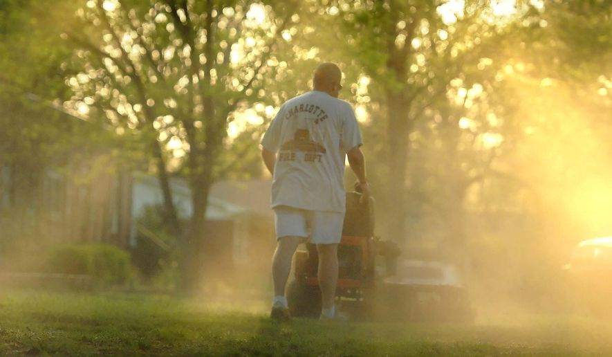FILE - In a Monday, April 5, 2010, file photo, Shane Nantz kicks up a cloud of pollen as he mows the front yard of his west Charlotte, N.C., home. (AP Photo/The Charlotte Observer, Todd Sumlin, File)