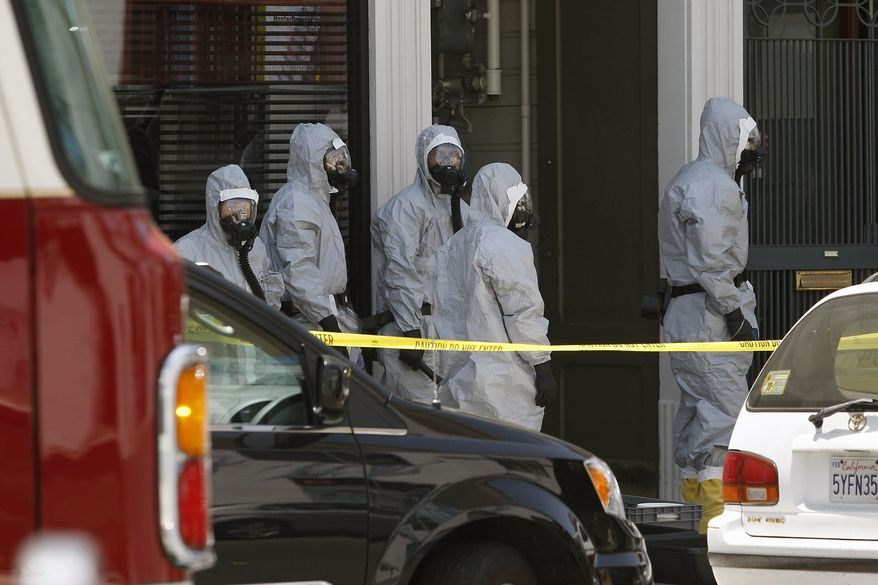 In this photo taken May 31, 2014, agents in hazardous material suits are seen as the FBI searches a building in San Francisco. A San Francisco social media maven and former political consultant who was wanted on suspicion of possessing explosives has been taken into custody after a three-day manhunt. Federal agents and the San Francisco police said they captured Ryan Kelly Chamberlain II, 42, on Monday, June 2, shortly after announcing that they had found his car near Crissy Field, just south of the Golden Gate Bridge. (AP Photo/San Francisco Chronicle, Michael Short) ORTHERN CALIFORNIA OUT; MANDATORY CREDIT PHOTOG & CHRONICLE; MAGS OUT; NO SALES