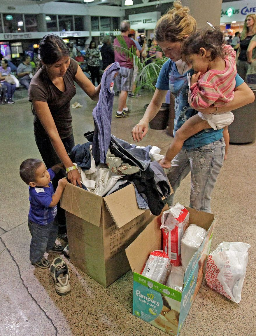 Families caught crossing from Mexico look through a box of donated clothing at the Greyhound bus terminal in Phoenix. Administration officials said they are trying to find ways to meet the law, which calls for immigration officials to turn over the children to the Health and Human Services Department within 72 hours after they are apprehended. (Associated press)