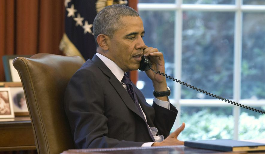 President Obama speaks on the phone in the Oval Office of the White House in Washington, June 2, 2014. (Associated Press) ** FILE **