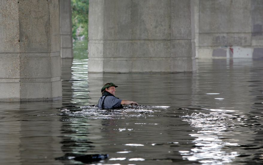 Times-Picayune staff photographer Alex Brandon swims away from the paper in the flooded city of New Orleans during the aftermath of Hurricane Katrina on Tuesday, Aug. 30, 2005. Brandon had swam to the building to get a memory card of photos to the paper.(AP Photo/Bill Haber)
