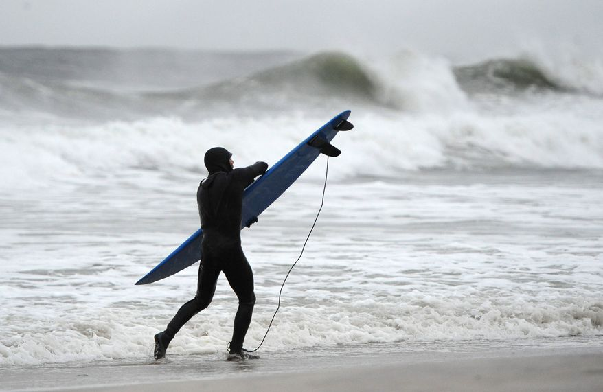 A surfer holds tight to his board against the strong winds and high surf of the Atlantic Ocean before the arrival of Hurricane Sandy on Sunday, Oct., 28, 2012, in Long Beach, N.Y. Tens of thousands of people were ordered to evacuate coastal areas Sunday as big cities and small towns across the U.S. Northeast braced for the onslaught of a superstorm threatening some 60 million people along the most heavily populated corridor in the nation. (AP Photo/Kathy Kmonicek)