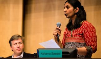Socialist Seattle City Council member Kshama Sawant, right, talks on Monday, June 2, 2014, at City Hall in Seattle. Phased in over the next seven years, Seattle will have the highest minimum wage in America. (AP Photo/seattlepi.com, Jordan Stead)