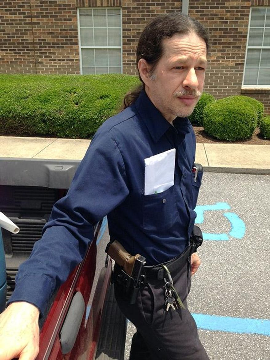 """Gun rights activist John David Murphy stands outside his voting precinct with his firearm in Alabaster, Ala., on Tuesday, June 3, 2014. Murphy ignored a """"no weapons"""" sign and entered to vote in Alabama's party primary with his weapon in his holster, but a deputy who made the man disarm before casting his ballot. (AP Photo/Jay Reeves)"""