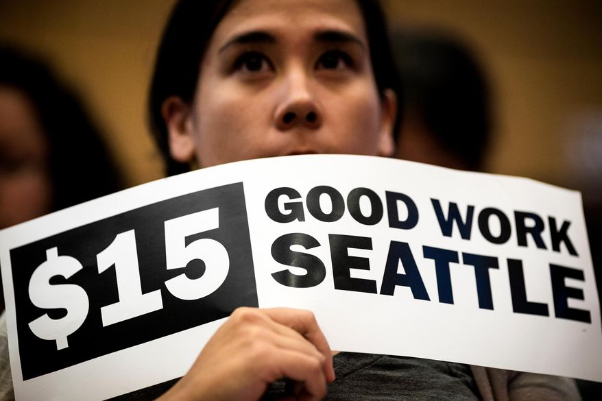 Hoisting signs, supporters showed support for the passage of increasing the minimum wage in the city to $15 for Seattle employers on Monday, June 2, 2014, at City Hall in Seattle. Phased in over the next seven years, Seattle will have the highest minimum wage in America. (AP Photo/seattlepi.com, Jordan Stead)