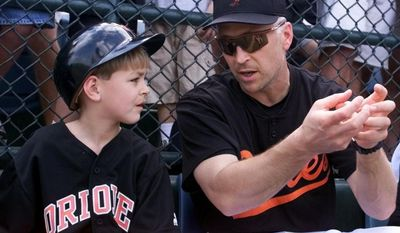 Baltimore Orioles' Cal Ripken explains to his son Ryan the duties of bat boy before a spring training game against the Minnesota Twins in Fort Lauderdale, Fla. Saturday, March 3, 2001.  Ripken cracked his ribs before arriving at training camp and did not play in the game.(AP Photo/Roberto Borea)