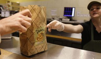 A worker passes an order to a customer at a Panera store in Brookline, Massachusetts. Panera has joined a growing list of restaurants asking gun owners to leave their artillery at home. (AP Photo/Charles Krupa, File)