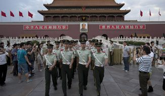 ** FILE ** In this May 28, 2014, photo, paramilitary policemen march out of Tiananmen Gate to clear tourists from the area for a flag-lowering ceremony on Tiananmen Square in Beijing. (AP Photo/Alexander F. Yuan)