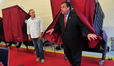 Election worker Norberto Rivera watches as Gov. Chris Christie emerges from the voting booth after voting in New Jersey's primary election at Mendham Township's Emergency Services Building Tuesday evening, June 3, 2014, with wife Mary Pat and daughter Sarah in Mendham Township, NJ.  (AP Photo/The Asbury Park Press, Karen Mancinelli)  NO SALES