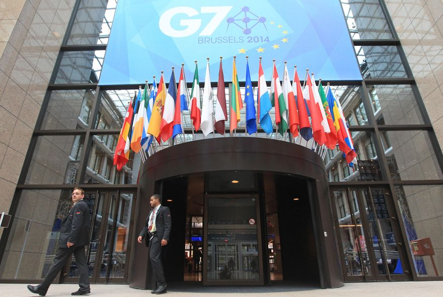 Two security guards pass the entrance of the European Council building in Brussels ahead of a two-day G7 meeting, Wednesday, June 4, 2014. The leaders of the G7 will deliberate their next steps in response to the enduring unrest in Ukraine, after sidelining Russia for its role in the crisis. (AP Photo/Yves Logghe)