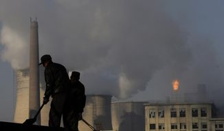 ** FILE ** In this Nov. 30, 2007, file photo, backdrop by cooling towers of a power plant and chemical factory, miners shovel coal at a mine in Xiahuayuan county, north China's Hebei province. (AP Photo/Oded Balilty, File)