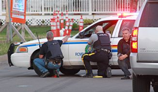 Police officers take cover behind their vehicles in Moncton, New Brunswick, on Wednesday June 4, 2014. Three police officers were shot dead and two others injured Wednesday in the east coast Canadian province of New Brunswick, officials said, and authorities were searching for a suspect. (AP Photo/Moncton Times & Transcript, Ron Ward via The Canadian Press ) MANDITORY CREDIT