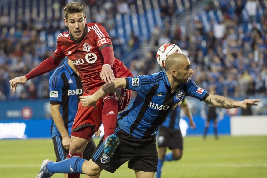 Toronto FC's Alvaro Rey leaps onto Montreal Impact's Marco Di Vaio during the first half of the Voyageurs Cup, Wednesday, June 4, 2014 in Montreal. (AP Photo/The Canadian Press, Paul Chiasson)