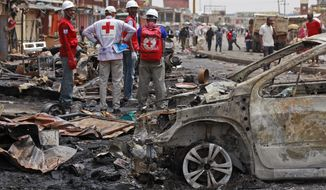 FILE-In this file photo taken on Wednesday, May 21, 2014, Red Cross personnel search for remains at the site of one of Tuesday's car bombs in Jos, Nigeria.  Boko Haram militants are taking over villages in northeastern Nigeria, killing and terrorizing civilians and political leaders, witnesses say, as the Islamic fighters make a comeback from a year-long military offensive aimed at crushing them.  (AP Photo/Sunday Alamba, File)