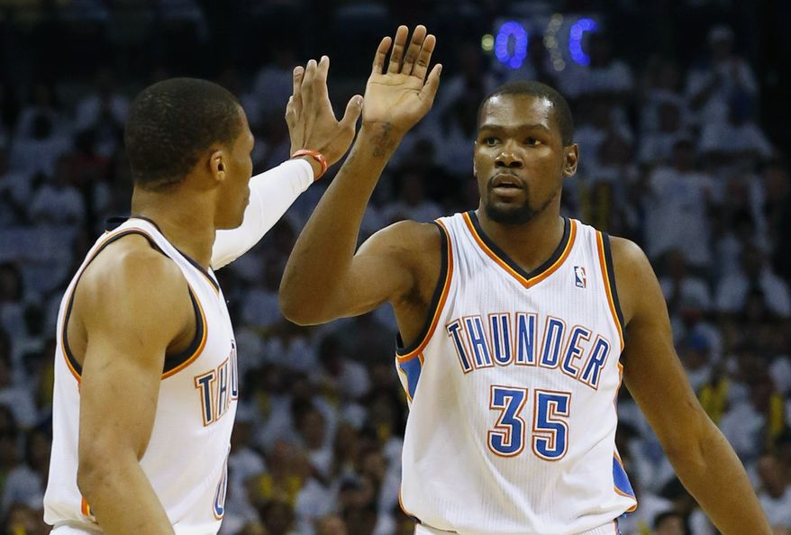 Oklahoma City Thunder's Russell Westbrook, left, and Kevin Durant celebrate during the first half against the San Antonio Spurs in Game 6 of the Western Conference finals NBA basketball playoff series in Oklahoma City, Saturday, May 31, 2014. (AP Photo/Sue Ogrocki)
