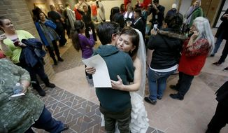 FILE - In this Dec 23, 2013, file photo, Jax and Heather Collins hug after getting married at the Salt Lake County Clerk's Office. Utah is appealing a federal judge's ruling that officials must recognize gay marriages that took place in the state after a same-sex marriage ban was overturned. Utah Gov. Gary Herbert and Attorney General Sean Reyes filed an appeal Wednesday, June 4, 2014, sending the case to the Denver-based 10th Circuit Court of Appeals. (AP Photo/Deseret News, Ravell Call, File)