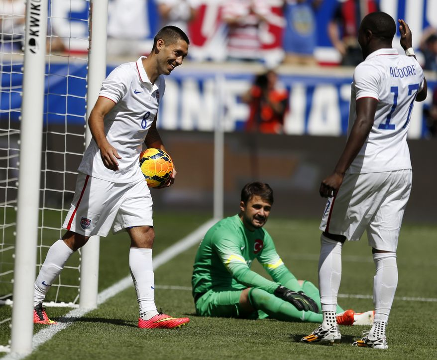 United States' Clint Dempsey, left, celebrates with teammate Jozy Altidore, right, after scoring a goal onTurkey goalkeeper Onur Recep Kivrak, center, in the second half of an international soccer friendly, Sunday, June 1, 2014, in Harrison, N.J. The U.S. won 2-1. (AP Photo/Julio Cortez)