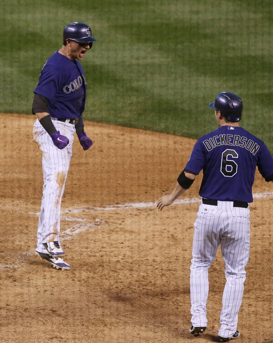 Colorado Rockies' Troy Tulowitzki (2) celebrates after scoring a run during the fifth inning of a baseball game against the Arizona Diamondbacks  Wednesday, June 4, 2014, in Denver. (AP Photo/Jack Dempsey)