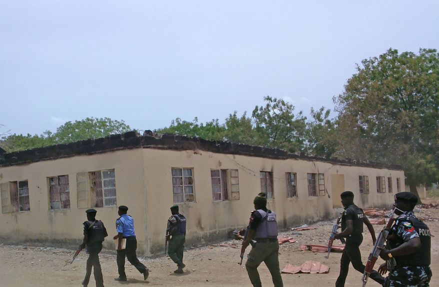 FILE - In this file photo taken on Monday, April, 21. 2014, security walk past  a burnt out government secondary school in Chibok, where gunmen abducted more than 200 students, Chibok, Nigeria.  Boko Haram militants dressed as soldiers slaughtered at least 200 civilians in three villages in northeastern Nigeria and the military failed to intervene even though it was warned that an attack was imminent, witnesses said on Thursday, June 5, 2014. (AP Photo/ Haruna Umar,File)