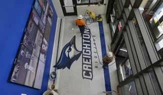 Workers put the final touches to the entry hall at Creighton University's newly built Championship Center in Omaha, Neb., Friday, June 6, 2014. The building is a training and academic support facility that is part of the east campus athletic-fitness-recreation corridor. (AP Photo/Nati Harnik)