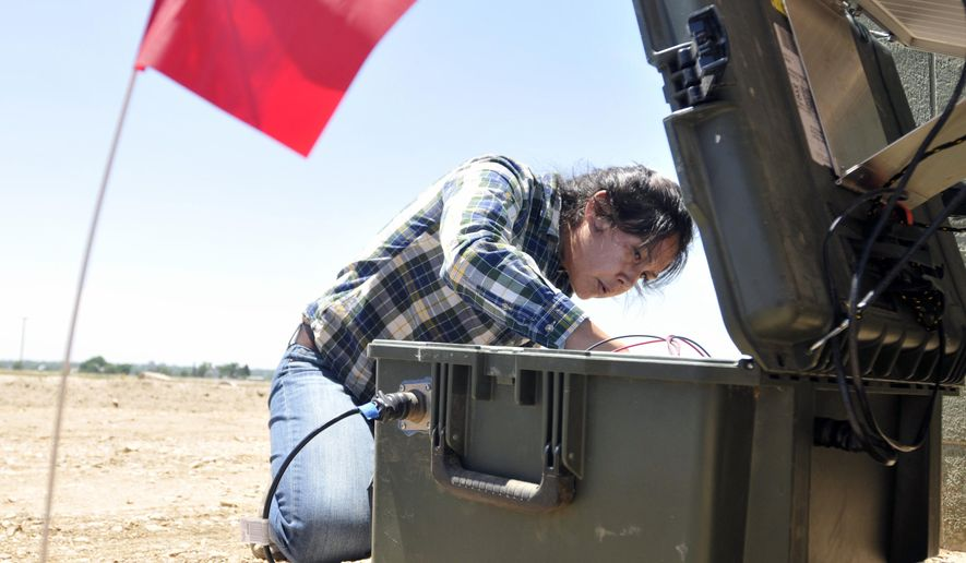 In this June 5, 2014 photo, a red flag marks the seismic monitor buried in the ground as Jenny Nakai, a graduate student in seismology from University of Colorado at Boulder, begins checking one of the instruments above near the intersection of Weld County Road 64 south of Lucerne, Colo. Anne Sheehan, a geophysicist from the University of Colorado is hoping to settle the question of whether a small earthquake last weekend near Greeley was caused by wastewater injection wells. (AP Photo/The Greeley Tribune, Joshua Polson)
