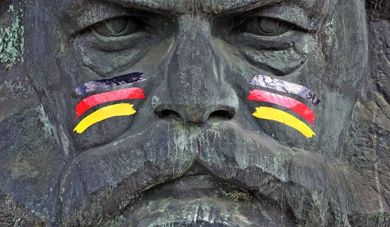 The monument of German philosopher, economist, and revolutionary socialist Karl Marx is painted with German national colors as an advertisement for the upcoming soccer World Cup tournament in Brazil, in Chemnitz, eastern Germany, Friday, June 6, 2014. (AP Photo/dpa,Jan Woitas) ** FILE **