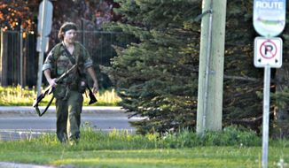 A heavily armed man that police have identified as Justin Bourque walks on Hildegard Drive in Moncton, New Brunswick, on Wednesday, June 4, 2014, after several shots were fired in the area. The man suspected in the shooting deaths of three Royal Canadian Mounted Police and the wounding of two others in a rare case of gun violence in eastern Canada was arrested early Friday, police said. (AP Photo/The Canadian Press, Moncton Times & Transcript, telegraphjournal.com, Viktor Pivovarov) MANDATORY CREDIT