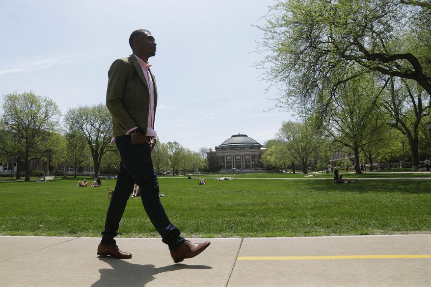 ** FILE ** In this May 8, 2014, photo, Cameron Barnes, a journalism graduate at the University of Illinois-Champaign, walks across campus during his final weeks at school. (AP Photo/Seth Perlman)