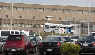 In this July 22, 2010, photo, public security buses wait at outside the prison at the Orsainville Detention Center in Quebec City, Quebec.  Police said on Saturday, June 7, 2014, that three inmates have escaped from the detention center in Quebec City with the help of a helicopter. (AP Photo/The Canadian Press, Jacques Boissinot)