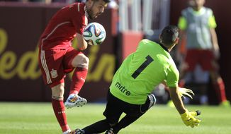 Spain's David Villa, left, kicks the ball as El Salvador goalkeeper  Derby Carrillo (1)  defends during the second half of an exhibition soccer game, Saturday, June 7, 2014, in Landover, Md. Spain won 2-0. (AP Photo/Luis M. Alvarez)