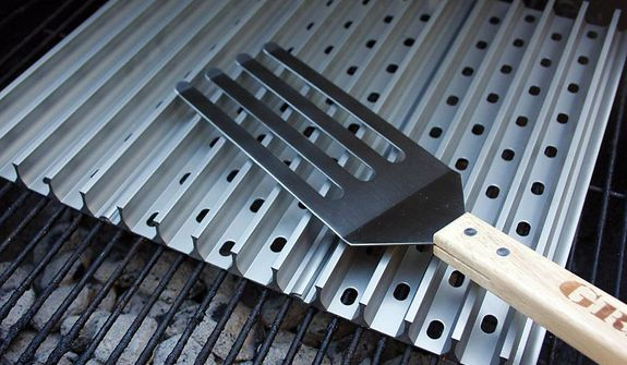 Dad can use a set of Grill Grates to help control the cooking of meat at the family barbeque.