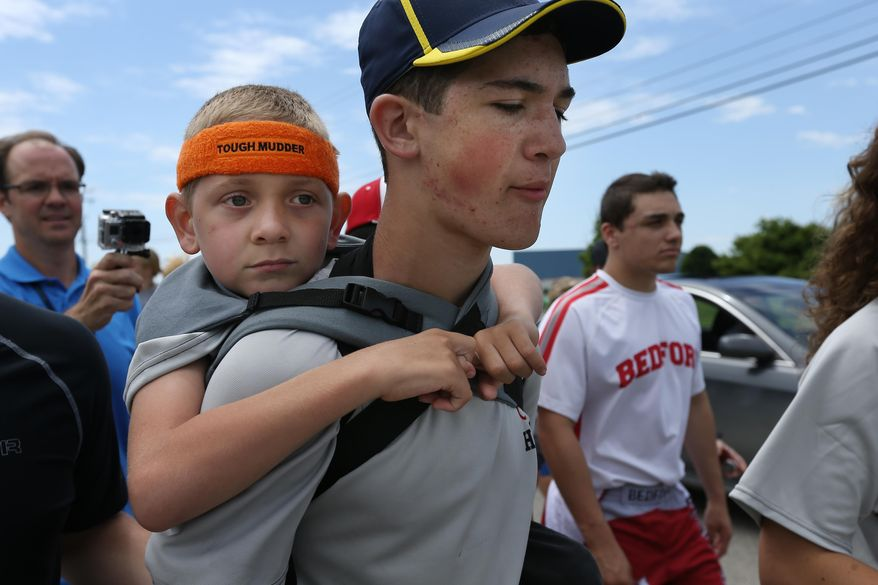 CORRECTS LAST NAME TO GANDEE - Braden Gandee, 7, rides on his brother Hunter's, 14, shoulders as they close in on the final miles to the University of Michigan Bahna Wrestler Center on Sunday, June 8, 2014. Hunter carried Braden, who has cerebral palsy, 40 miles from Bedford, Mich. to Ann Arbor, Mich. (AP Photo/The Ann Arbor News, Chris Asadian)