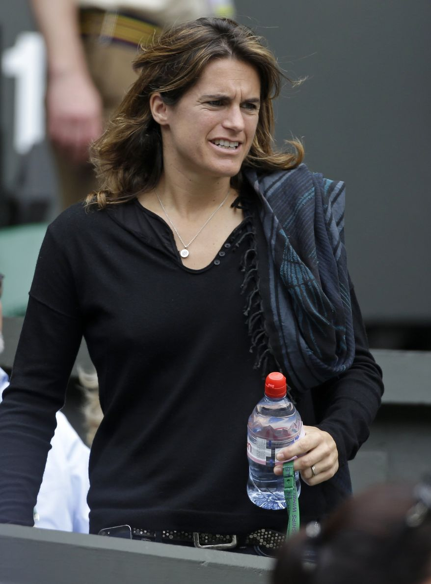 Retired tennis player Amelie Mauresmo arrives to watch Marion Bartoli of France face Kirsten Flipkens of Belgium in a Women's singles semifinal match at the All England Lawn Tennis Championships in Wimbledon, London, Thursday, July 4, 2013. (AP Photo/Anja Niedringhaus)