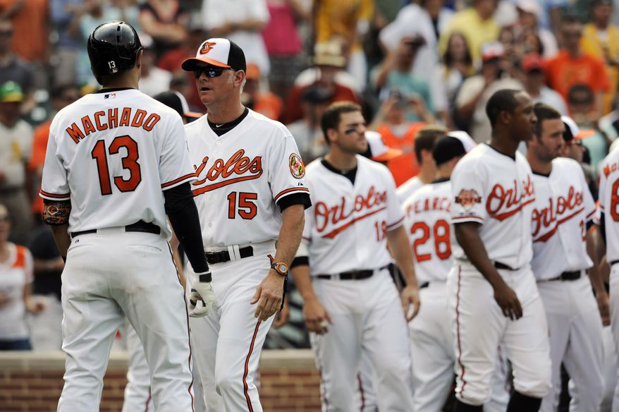 Baltimore Orioles batting coach Jim Presley, (15) keeps Manny Machado, (13) away from the Oakland Athletics after the benches cleared in the eighth inning of a baseball game, Sunday, June 8, 2014, in Baltimore. The benches cleared after Machado threw his bat into the infield after an inside pitch was thrown at him. The Athletics won 11-1. (AP Photo/Gail Burton)