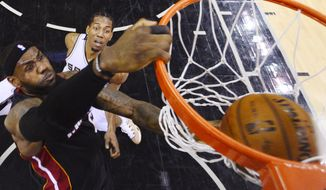 Miami Heat forward LeBron James dunks as San Antonio Spurs forward Kawhi Leonard looks on during the first half in Game 2 of the NBA basketball finals on Saturday, Nov. 8, 2014, in San Antonio. (AP Photo/Larry W. Smith, pool)